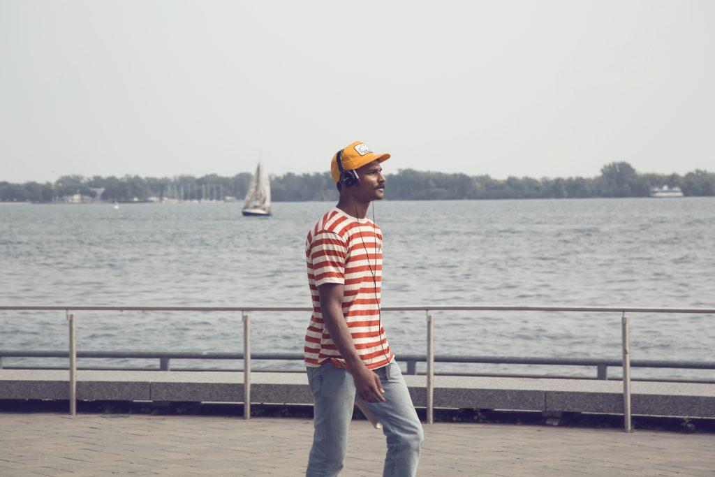 Man in striped shirt walking on dock in harbourfront, toronto