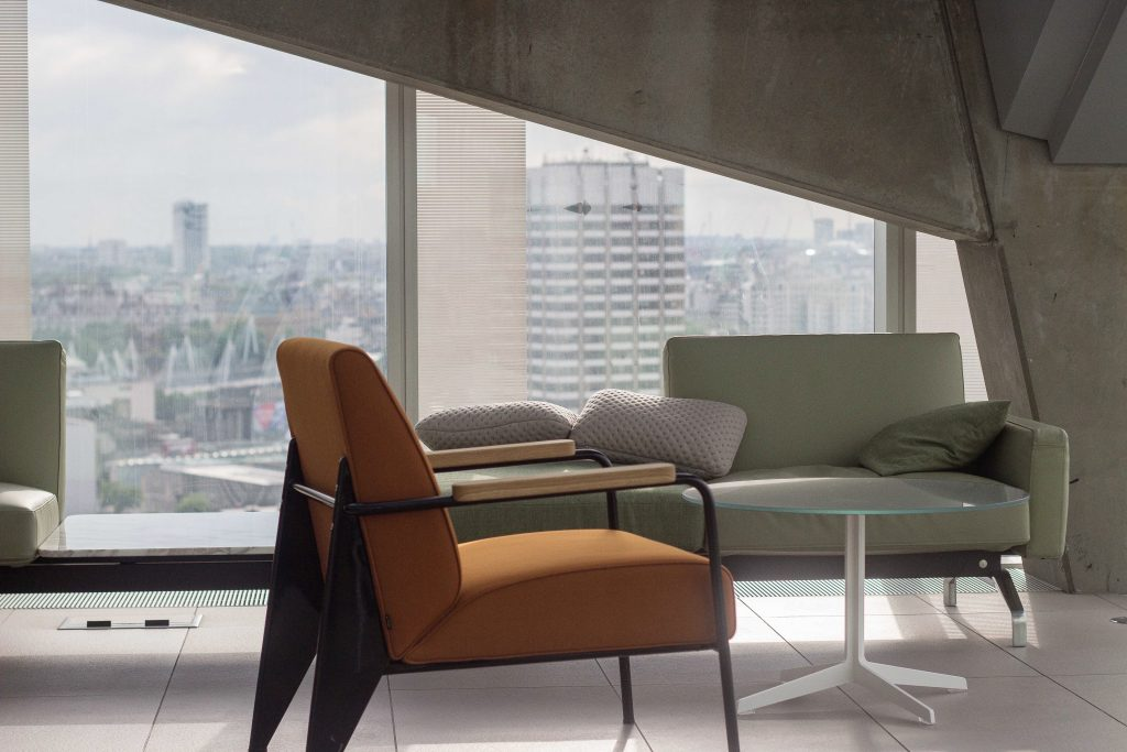 orange and green sofas in condo with glass table