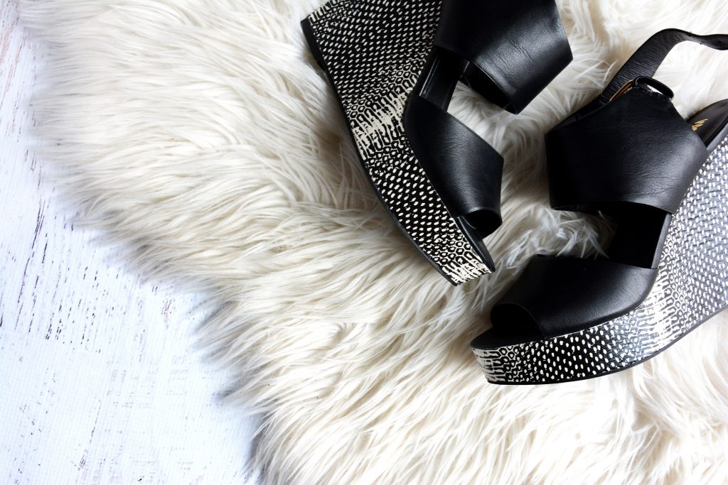 Black wedges with silver detailing on white furry carpet