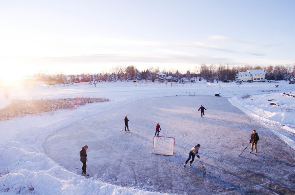 People playing hockey on frozen over pond