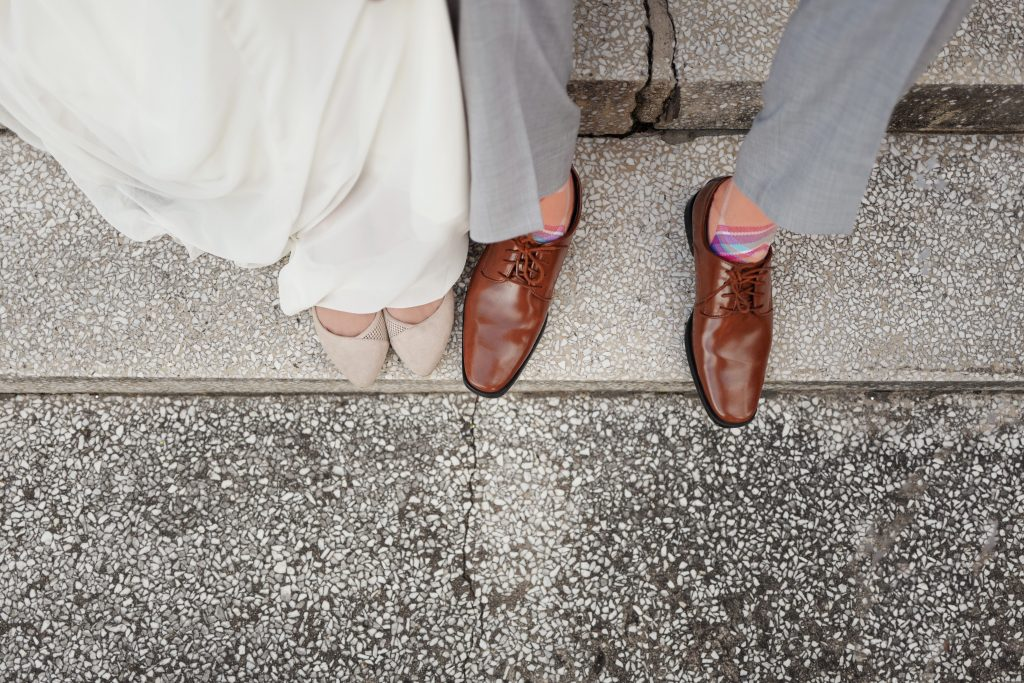 view looking down on man and woman's feet, with brown leather and beige shoes on steps