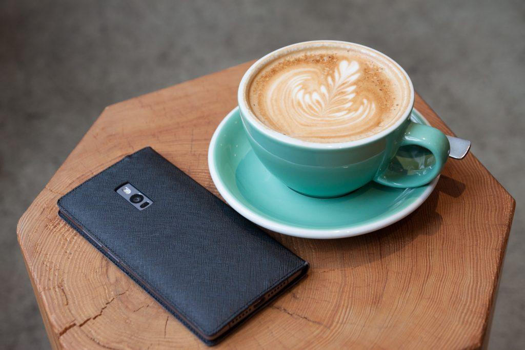 blue mug on coaster with coffee beside black smartphone