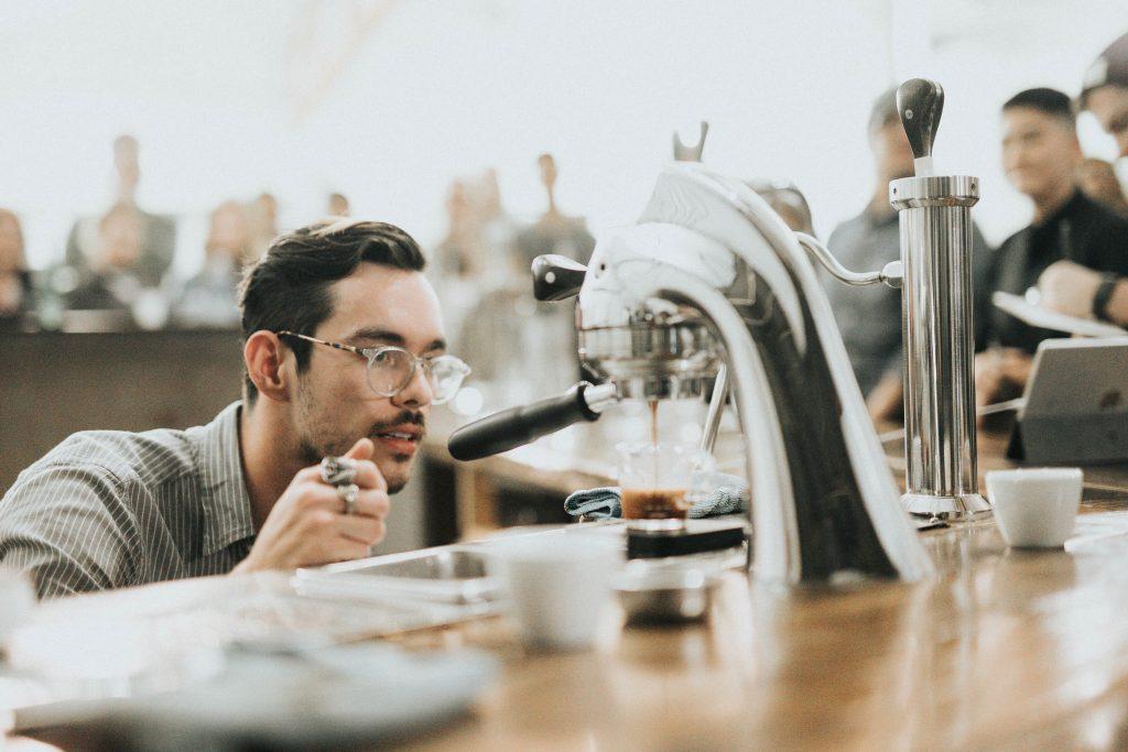 man making coffee drink at bar