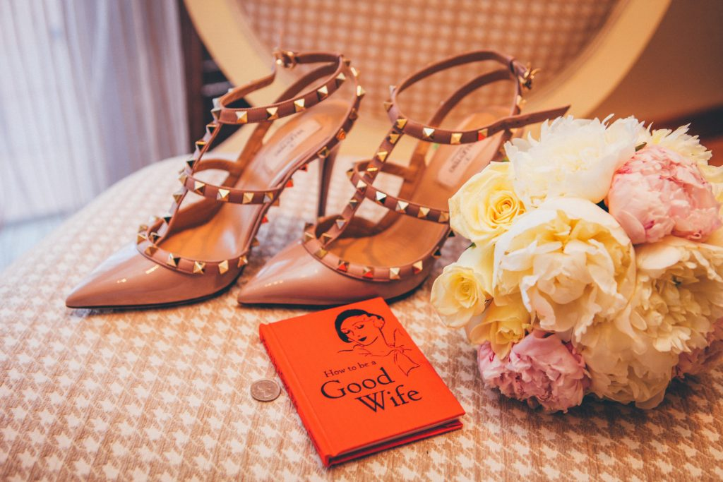 spiked high heels next to flowers and a book titled 'how to be a good wife'
