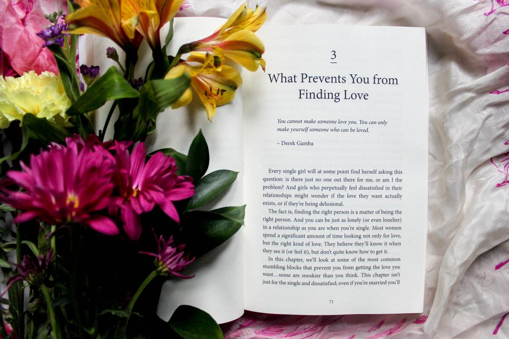 "book open on chapter three ""what prevents you from finding love"" with flowers"